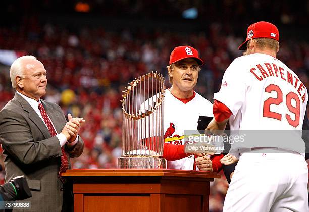 Chris Carpenter of the St Louis Cardinals is presented with his 2006 World Series Championship ring by manager Tony LaRussa as GM Walt Jocketty looks...