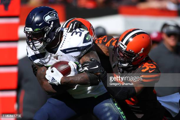 Chris Carson of the Seattle Seahawks battles through a tackle by Jermaine Whitehead of the Cleveland Browns during a third quarter run at FirstEnergy...