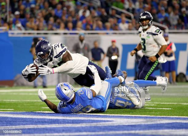 Chris Carson of the Seattle Seahawks bowls over Quandre Diggs of the Detroit Lions for a touchdown during the fourth quarter at Ford Field on October...