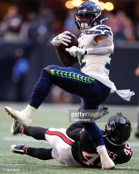 Chris Carson of the Seattle Seahawks breaks away from Deion Jones of the Atlanta Falcons in the first half of an NFL game at Mercedes-Benz Stadium on...