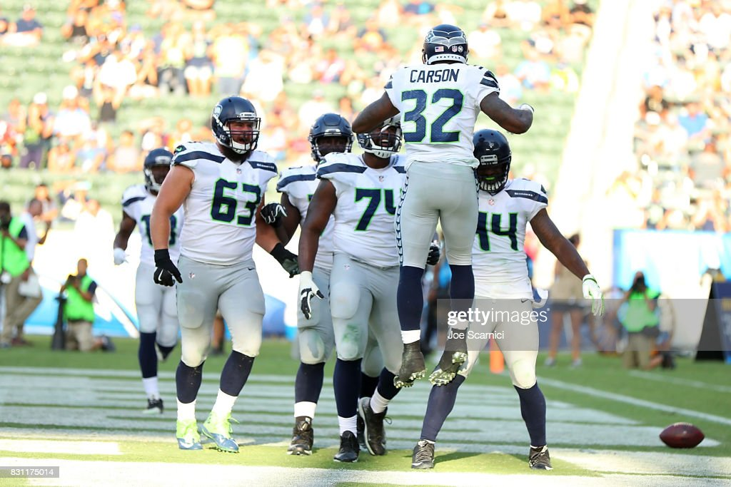 Chris Carson #32 of the Seattle Seahawks celebrates a touchdown with teammates in the second quarter against the Los Angeles Chargers at StubHub Center on August 13, 2017 in Carson, California.