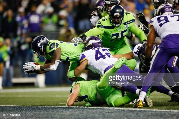Chris Carson of the Seattle Seahawks dives passed Ben Gedeon of the Minnesota Vikings for a touchdown in the fourth quarter at CenturyLink Field on...