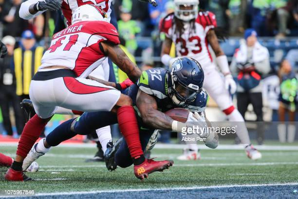 Chris Carson of the Seattle Seahawks dives past Antoine Bethea of the Arizona Cardinals for a touchdown in the second quarter at CenturyLink Field on...