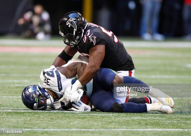 Chris Carson of the Seattle Seahawks is brought down by Grady Jarrett of the Atlanta Falcons in the second half of an NFL game at Mercedes-Benz...