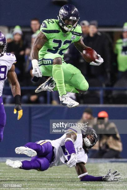 Chris Carson of the Seattle Seahawks leaps over a Minnesota Vikings defender in the second quarter at CenturyLink Field on December 10 2018 in...