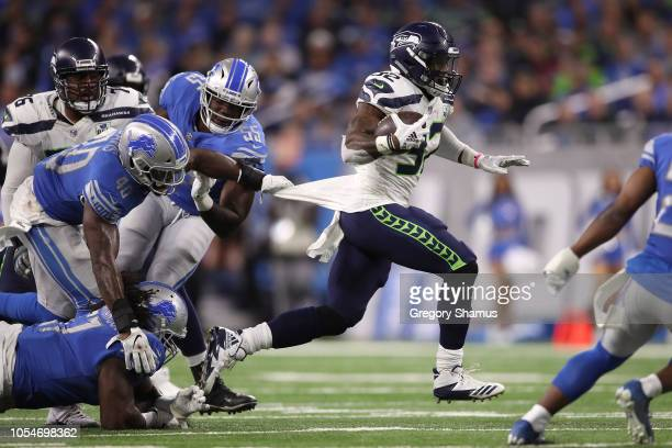 Chris Carson of the Seattle Seahawks looks to run the ball against Jarrad Davis of the Detroit Lions and Eric Lee during the first half at Ford Field...
