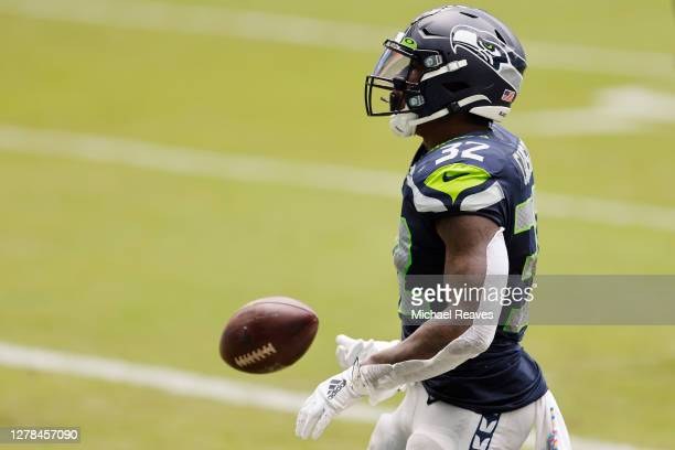 Chris Carson of the Seattle Seahawks reacts after scoring a touchdown against the Miami Dolphins during the first quarter at Hard Rock Stadium on...