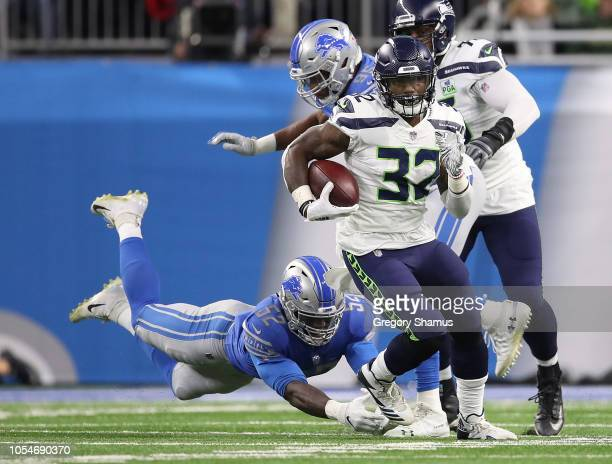 Chris Carson of the Seattle Seahawks runs for yardage in front of a diving Christian Jones of the Detroit Lions at Ford Field on October 28 2018 in...
