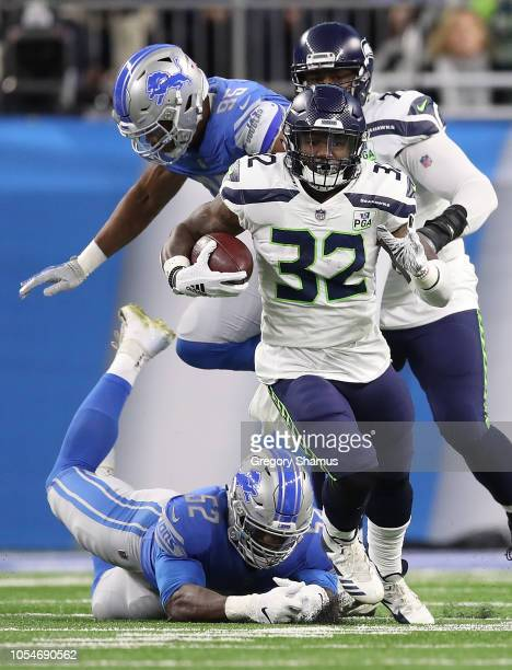 Chris Carson of the Seattle Seahawks runs for yardage in front of a diving Christian Jones of the Detroit Lions during the second quarter at Ford...