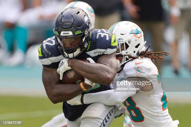 Chris Carson of the Seattle Seahawks runs with the ball against Bobby McCain of the Miami Dolphins during the second half at Hard Rock Stadium on...