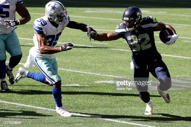 Chris Carson of the Seattle Seahawks runs with the ball against Brandon Carr of the Dallas Cowboys during the second quarter in the game at...
