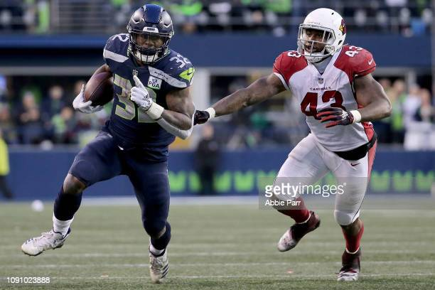 Chris Carson of the Seattle Seahawks runs with the ball against Haason Reddick of the Arizona Cardinals in the fourth quarter during their game at...