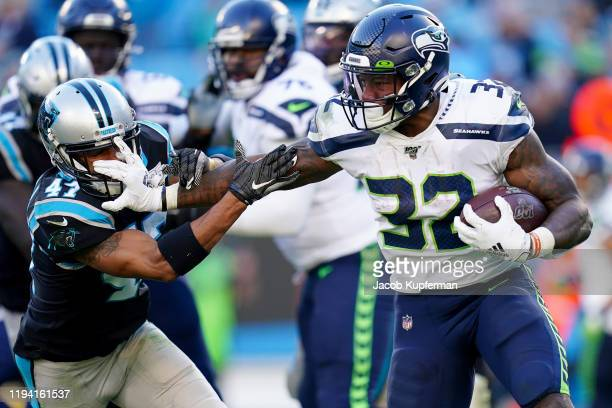 Chris Carson of the Seattle Seahawks stiff arms Ross Cockrell of the Carolina Panthers in the fourth quarter during their game at Bank of America...