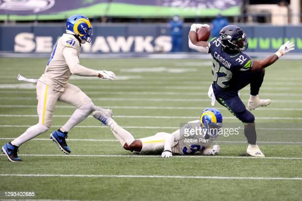Chris Carson of the Seattle Seahawks stumbles after being pushed by Darious Williams of the Los Angeles Rams in the second quarter at Lumen Field on...