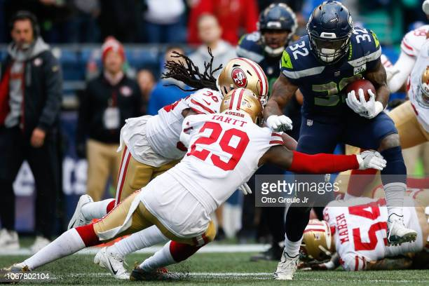 Chris Carson of the Seattle Seahawks tries to avoid a tackle by Jaquiski Tartt of the San Francisco 49ers in the first half at CenturyLink Field on...