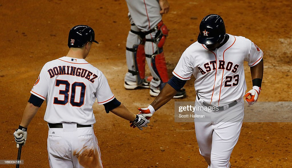 Chris Carter #23 and Matt Dominguez #30 of the Houston Astros celebrate after Carter hit a solo home run against the Los Angeles Angels of Anaheim in the fifth inning at Minute Maid Park on May 8, 2013 in Houston, Texas.
