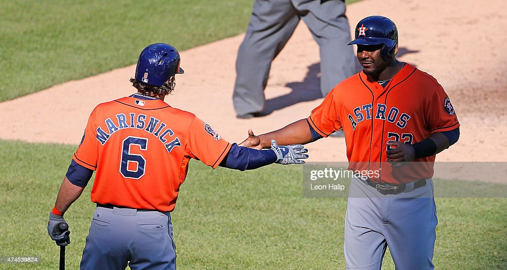 Chris Carter #23 of the Houston Astros scores on the single by Marwin Gonzalez #9 (not in photo) and is congratulated by teammate Jake Marisnick #6 during the sixth inning of the game against the Detroit Tigers on May 23, 2015 at Comerica Park in Detroit, Michigan.