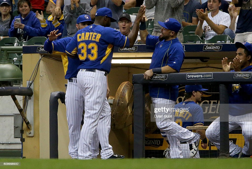 Chris Carter #33 of the Milwaukee Brewers is congratulated by teammates after turning a triple play in the first inning against the Cincinnati Reds at Miller Park on September 23, 2016 in Milwaukee, Wisconsin.