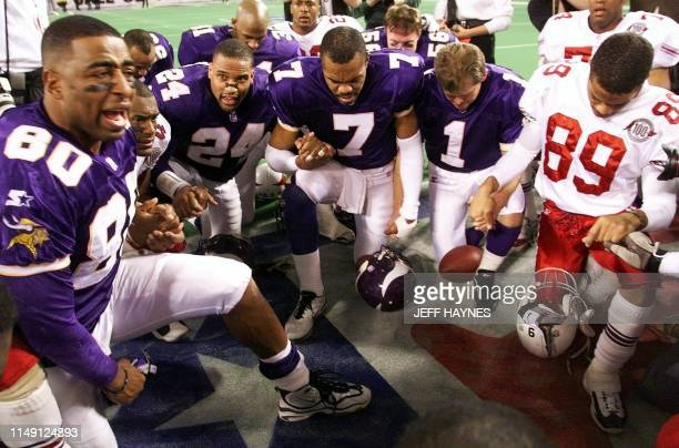 Chris Carter of the Minnesota Vikings leads teammates and members of the Arizona Cardinals in prayer 10 January after their NFC Divisional playoff...