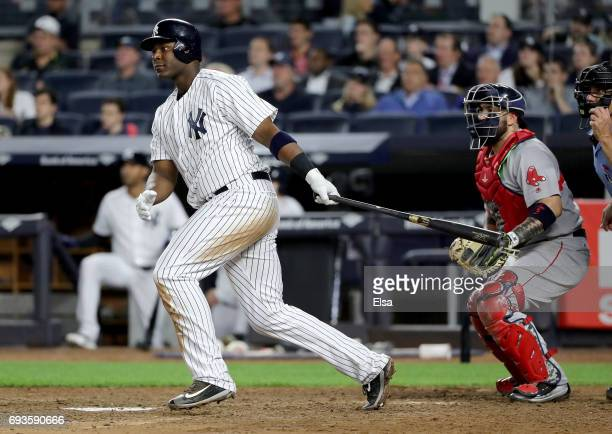 Chris Carter of the New York Yankees drives in a run in the eighth inning as Sandy Leon of the Boston Red Sox defends on June 7 2017 at Yankee...