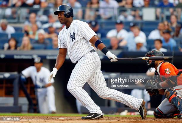 Chris Carter of the New York Yankees follows through on a first inning run scoring base hit against the Baltimore Orioles at Yankee Stadium on June...