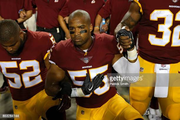 Chris Carter of the Washington Redskins kneels with his hand over his heart during the national anthem before playing against the Oakland Raiders at...