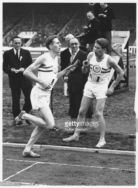 Chris Chataway, with watch in hand, yells the time into the ear of the running Bannister during the 4x100 relay in which the British team of...