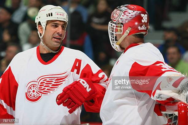 Chris Chelios of the Detroit Red Wings talks with teammate Dominik Hasek during a break in action of their NHL game against the Vancouver Canucks on...