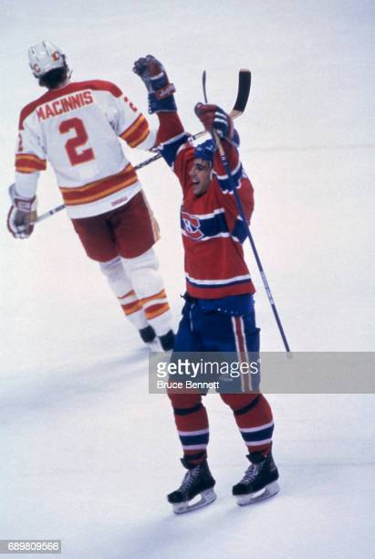 Chris Chelios of the Montreal Canadiens celebrates on the ice as Al MacInnis of the Calgary Flames skates away dejected during a game in the 1986...