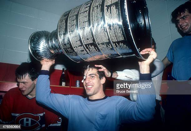Chris Chelios of the Montreal Canadiens celebrates while holding the Stanley Cup Trophy and having champagne poured over his head in the locker room...