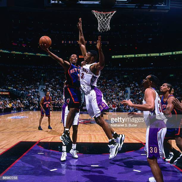 Chris Childs of the New York Knicks shoots a layup against Antonio Davis of the Toronto Raptors in Game Three of the Eastern Conference Quarterfinals...