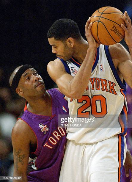 Chris Childs of the Toronto Raptors looks up at Allan Houston of the New York Knicks as Houston guards the ball in the first quarter of their NBA...
