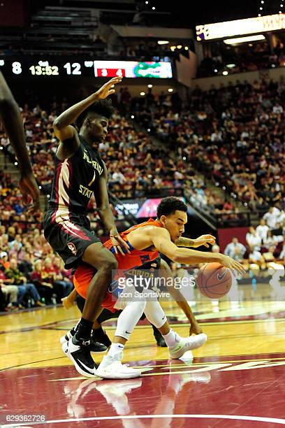 Chris Chiozza guard Florida Gators attempts to dribble past Jonathan Isaac forward Florida State University Seminoles in the Sunshine Shootout on...