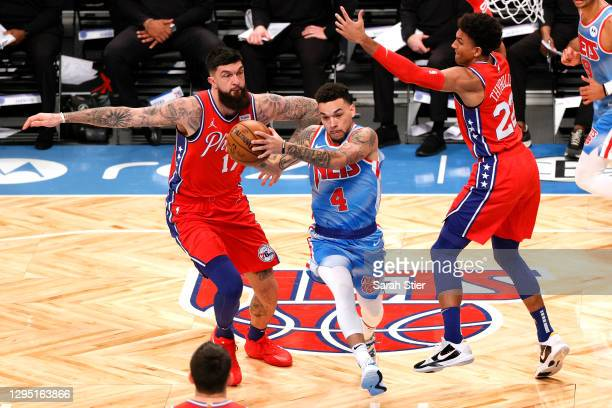 Chris Chiozza of the Brooklyn Nets drives to the basket as Vincent Poirier and Matisse Thybulle of the Philadelphia 76ers defend during the second...