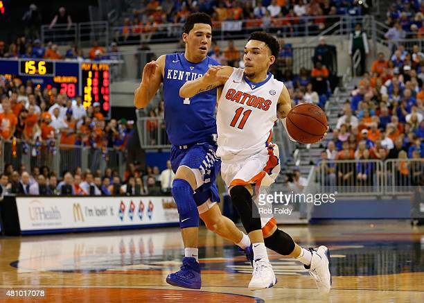 Chris Chiozza of the Florida Gators and Devin Booker of the Kentucky Wildcats in action during the game at the Stephen C O'Connell Center on February...