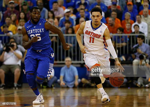 Chris Chiozza of the Florida Gators and Dominique Hawkins of the Kentucky Wildcats in action during the game at the Stephen C O'Connell Center on...