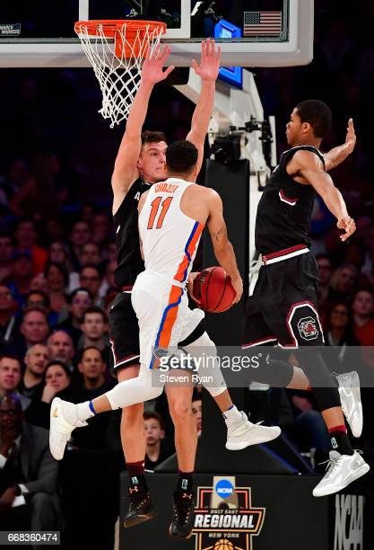 Chris Chiozza of the Florida Gators attempts a shot defended by Maik Kotsar and PJ Dozier of the South Carolina Gamecocks during the second half of...
