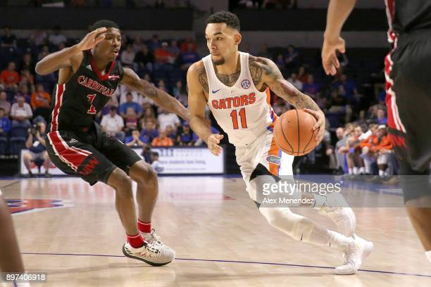 Chris Chiozza of the Florida Gators drives past Jalin Hart of the Incarnate Word Cardinals during a NCAA basketball game at the Stephen C O' Connell...