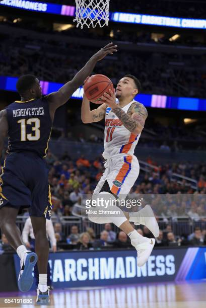 Chris Chiozza of the Florida Gators drives to the basket against AJ Merriweather of the East Tennessee State Buccaneers during the first round of the...