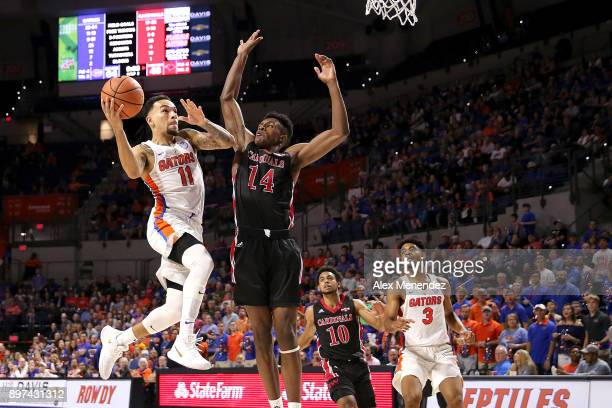 Chris Chiozza of the Florida Gators drives to the basket against Keaton Hervey of the Incarnate Word Cardinals during a NCAA basketball game at the...