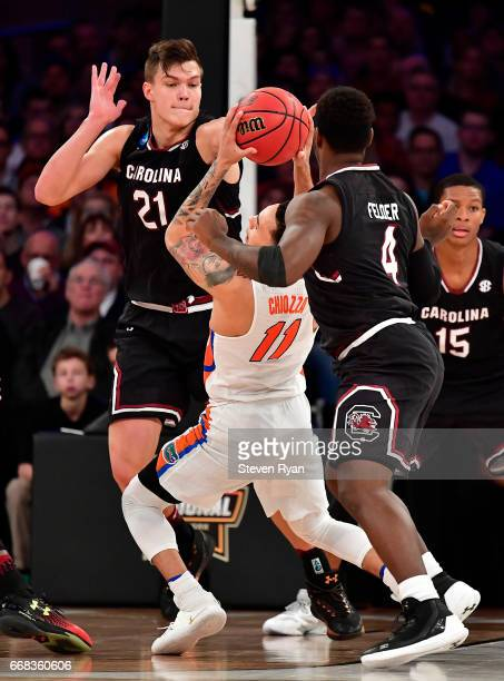 Chris Chiozza of the Florida Gators is defended by Maik Kotsar of the South Carolina Gamecocks during the second half of the 2017 NCAA Men's...