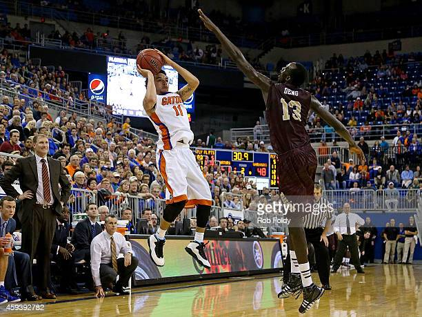 Chris Chiozza of the Florida Gators looks to pass around Majok Deng of the Louisiana Monroe Warhawks during the second half of the game at Stephen C...