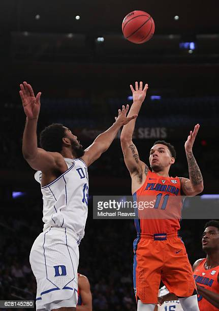Chris Chiozza of the Florida Gators puts up a floater over Matt Jones of the Duke Blue Devils in the first half during the Jimmy V Classic at Madison...
