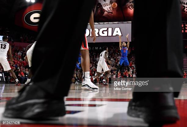 Chris Chiozza of the Florida Gators shoots over Tyree Crump of the Georgia Bulldogs during the basketball game at Stegeman Coliseum on January 30...