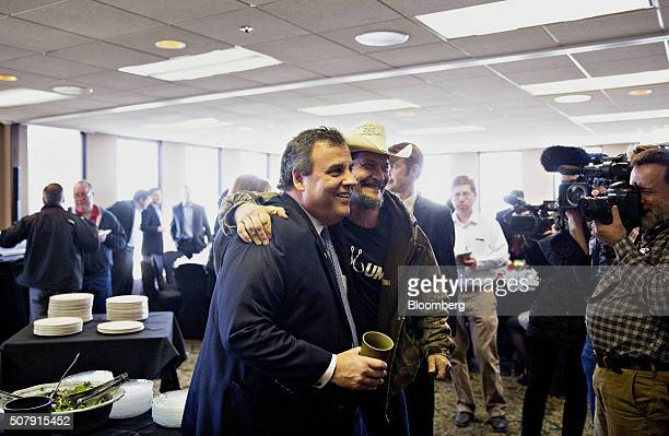 Chris Christie governor of New Jersey and 2016 Republican presidential candidate left stands for a photograph with a supporter after speaking during...