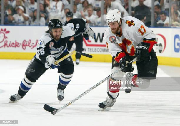 Chris Clark of the Calgary Flames controls the puck in front of Martin St Louis of the Tampa Bay Lightning during the third period in game five of...