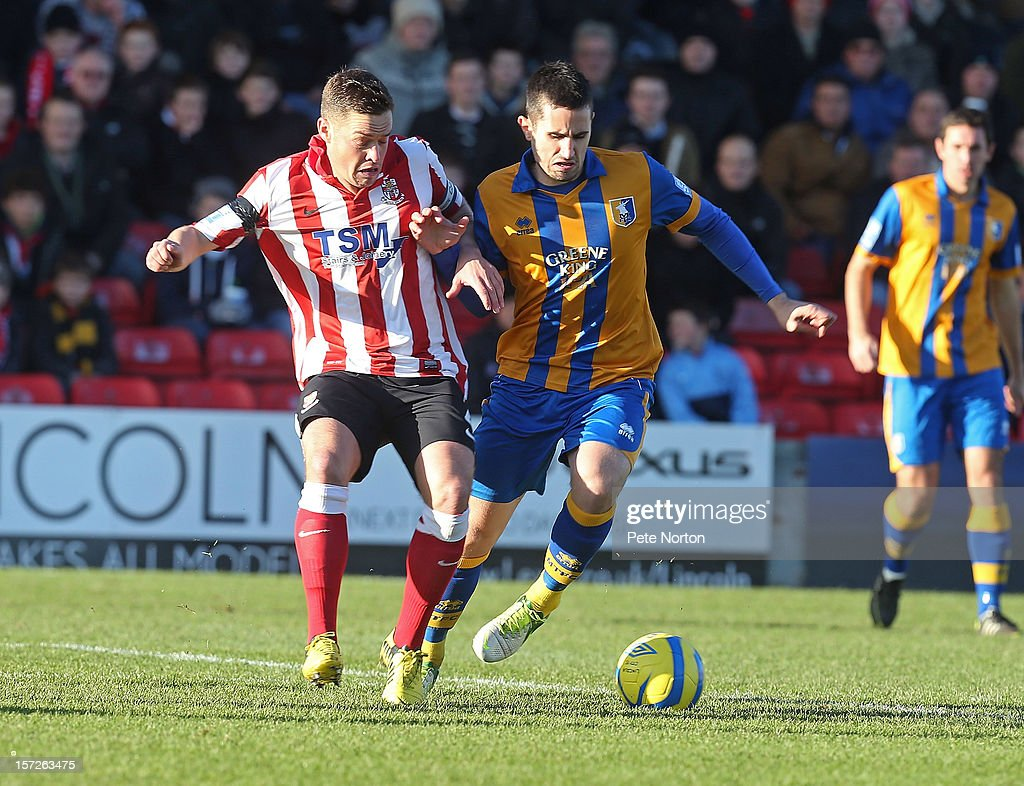 Chris Clements of Mansfield Town competes for the ball with Gary Mills of Lincoln City during the FA Cup with Budweiser Second Round match between Lincoln City and Mansfield Town at Sincil Bank Stadium on December 1, 2012 in Lincoln, England.