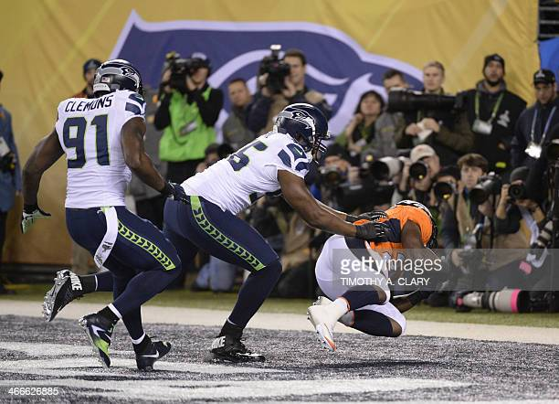 Chris Clemons and Cliff Avril of the Seattle Seahawks put pressure on Knowshon Moreno of the Denver Broncos for a safety on the first play of Super...