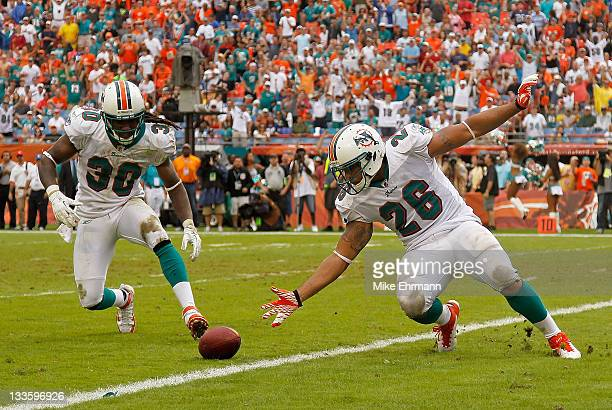 Chris Clemons and Lex Hilliard of the Miami Dolphins chase a blocked punt during a game against the Buffalo Bills at Sun Life Stadium on November 20...