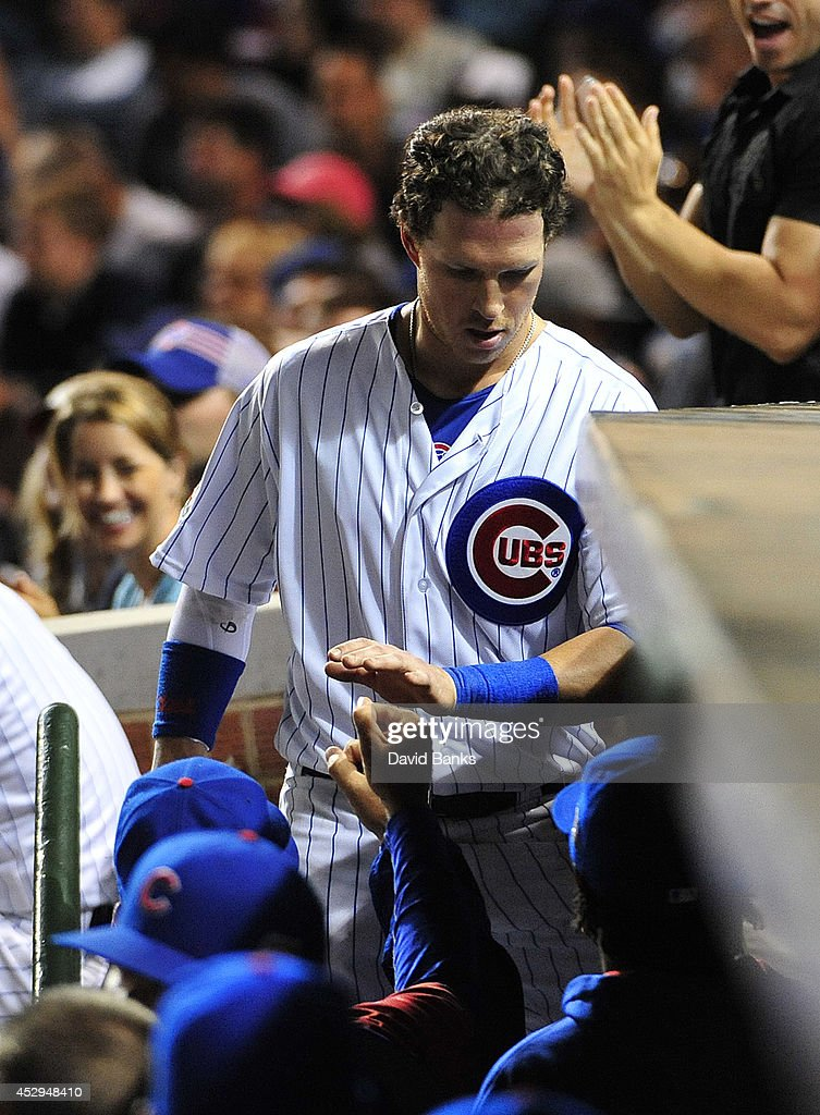 Chris Coghlan #8 of the Chicago Cubs is greeted in the dugout after scoring against the Colorado Rockies during the sixth inning on July 30, 2014 at Wrigley Field in Chicago, Illinois.